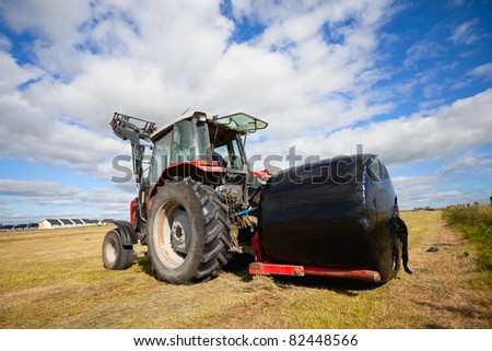 huge tractor collecting a roll haystack in the field in a nice blue sunny day