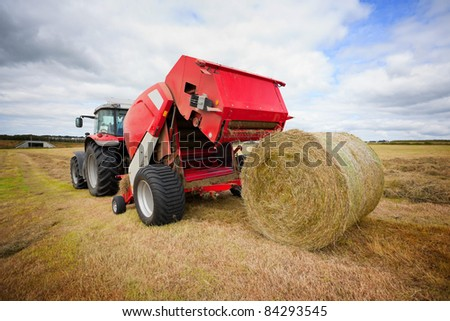 huge tractor collecting haystack in the field at nice blue sunny day
