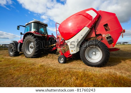 huge tractor collecting haystack in the field in a nice blue sunny day, panning technique