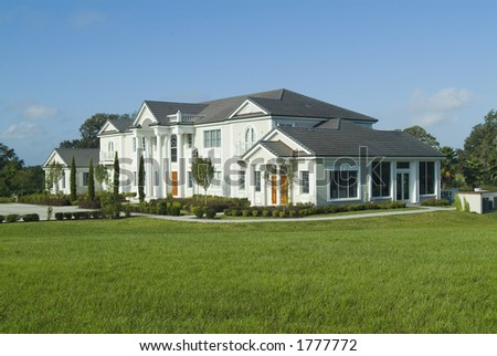 Huge upscale American house/mansion with beautiful landscaping - stock photo