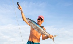 Huge Wahoo (spanish mackerel, king fish) trolling on a sailing yacht. Happy fisherman in shorts with his trophy on background of white boat deck. Fishing in Indian ocean near Phuket island, Thailand