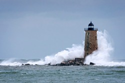 Huge waves crash around Whaleback lighthouse after storm tidal surge in Maine. Waves created by astronomically high tides after storm passes.