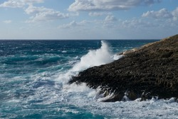 Huge waves crashing on the rocks in Malta, Zurieq. Huge wave explosion onto rocks. Large wave crash against the rocks during a storm in the tropics. Huge waves crash on cloudy day. Malta.Popular place