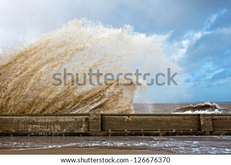 Huge waves crashing onto promenade on a stormy day
