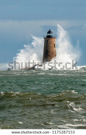 Huge waves surround stone lighthouse tower of Whaleback light in Maine during a unique high tide in early Spring. Vertical orientation. #1175287153
