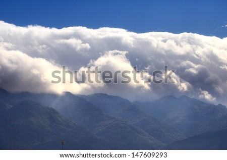 huge white cloud over mountain peak,dali,China