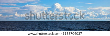 Huge white clouds in a blue sky over a dark ocean. Panorama