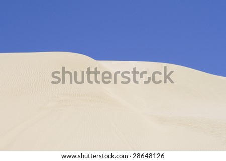 Huge white sand dune against blue sky
