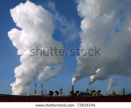 Huge white smoke from the pipes metallurgical plant, the blue sky - stock photo