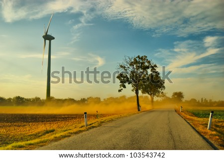 Huge wind turbine in the field throw up dust
