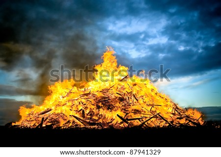 huge wood fueled bonfire burning at sunset