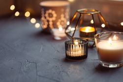 Hugge mood. Cozy background with candles and festive garland, closeup. Bokeh lights