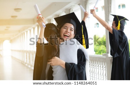 Hugging her friend,Student in mortarboard feeling hugging her friend,Graduate in mortarboard. Smiling graduate wearing mortarboard feeling unforgettable while hugging her friend,friendship,