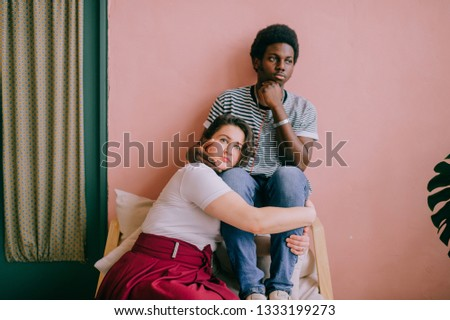 Hugging interracial couple lifestyle indoor portrait on pink wall background. Dark skinned nigerian man in striped shirt embracing his white girlfriend in red dress at home. International friendship