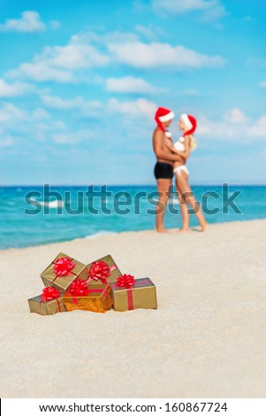 hugging lovers couple in santa hats at sea sandy beach with christmas packed  golden gifts