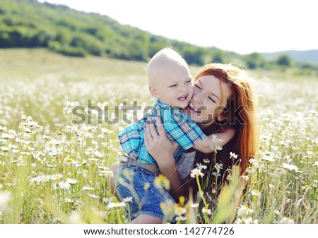 hugging mother and son in daisy field