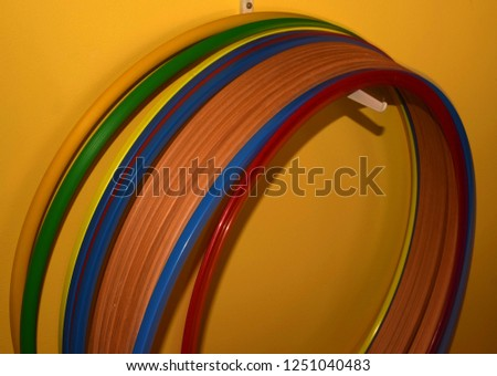 hula hoops in a row, hula hoops made of different materials and colors hanging on a hook in front of yellow background #1251040483