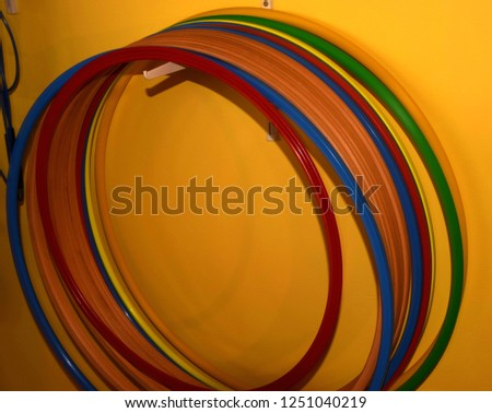 hula hoops made of different materials and colors hanging on a hook in front of yellow background, different hula hoops #1251040219