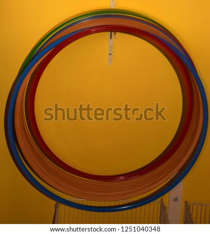 hula hoops without people, hula hoops made of different materials and colors hanging on a hook in front of yellow background #1251040348