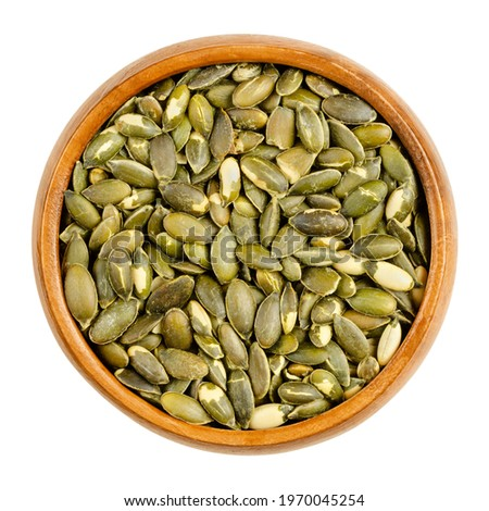 Hulled, roasted, salted pumpkin seeds, in a wooden bowl. Edible, flat, green squash seeds, also known as pepitas, used as a snack. Close-up, from above, isolated on white background, macro food photo. Foto stock ©