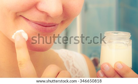 Human applying cleansing moisturizing skin cream on face. Person taking care of dry complexion layering moisturizer. Skincare. Instagram filter.
