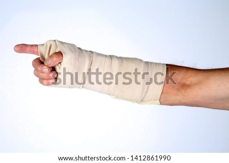 Human Arm in Cast. A human arm and hand wrapped in bandages with finger pointing. Room for text. Isolated on white. Emergency and Health Care or Insurance Claim concept.