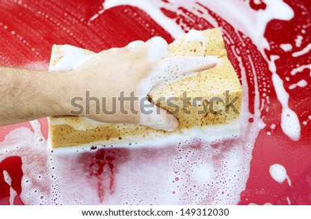 Human arm with sponge soap washing red car surface