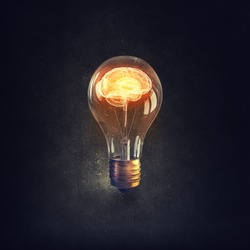Human brain glowing inside of light bulb on dark background