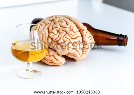 human brain with alcohol drinks and finished bottle, on white background
