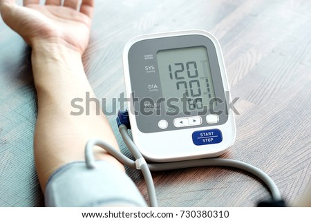 Human check blood pressure monitor and heart rate monitor with digital pressure gauge. Health care and  Medical concept #730380310
