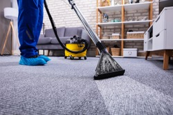 Human Cleaning Carpet In The Living Room Using Vacuum Cleaner At Home