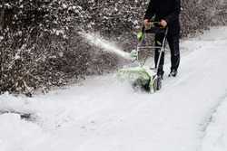 Human cleans snow off path with wireless electric snow blower after the winter snowfall