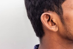 Human Ear - Close up of man ear Its body part helps to hearing sound waves. Face with a human ear and hair. Portrait of indian man and shoes on his ears isolated on white background with copy space.