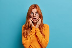 Human emotions and feelings concept. Speechless redhead woman keeps hands near opened mouth reacts to shocking news stares wondered at camera dressed in casual jumper poses indoor over blue wall