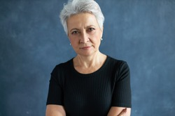 Human emotions and feelings. Headshot of casually dressed 60 year old retired female with gray hair keeping arms crossed on chest, staring at camera with scrutinizing suspicious look, narrowing eyes