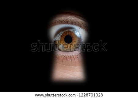 Human eye behind door is looking through a keyhole.