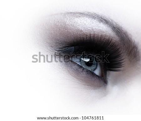 Human eye with eyelashes over white background