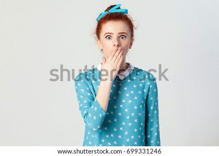 Human face expressions and emotions. Female in despair and shock. The young redhead girl in shocked, looking panic, covered her mouth by hand. Isolated studio shot on gray background. #699331246