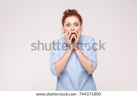 Human face expressions and emotions. Redhead young adult  woman holding arms on her cheeks and shocked. Isolated studio shot on gray background. #744371800