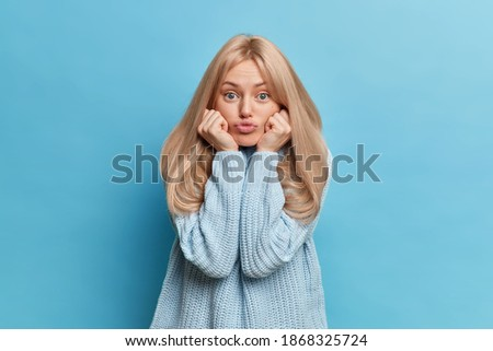 Human face expressions concept. Blonde funny adult woman folds lips keeps hands under chin gazes attentively at camera has concentrated look wears knitted sweater isolated over blue background Stockfoto ©