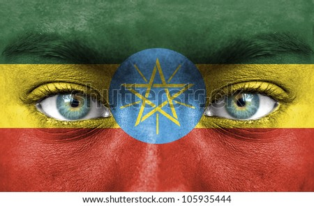 Human face painted with flag of Ethiopia - stock photo