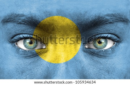 Human face painted with flag of Palau
