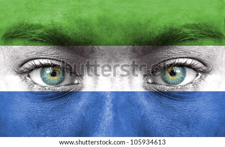 Human face painted with flag of Sierra Leone - stock photo