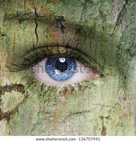 human face with an open eye covered in a tree bark texture