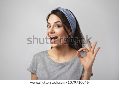 Human facial expressions and body language. Picture of positive friendly looking young woman in good mood exclaiming excitedly and making ok gesture, totally agreeing or understanding something