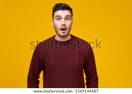 Human facial expressions and emotions. Shocked emotional young male in knitted jumper expressing full disbelief, surprised with big sale prices on Black Friday, staring at camera with astonishment #1569144487