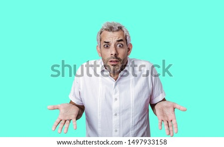 Human facial expressions concept. Satisfied young male with positive expression, attracts your attention at copy space aside, demonstrates some items in shop, has dark straight hair, isolated on color