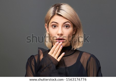 Human facial expressions, emotions and feelings. Gorgeous cute European female with blonde hair expressing genuine surprise and shock, opening mouth and popping eyes out, being in full disbelief #1563176776