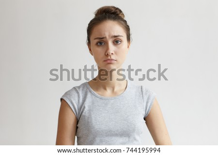 Human facial expressions, emotions, feelings and attitude. Unhappy sad young woman with hair gathered in bun feeling sorry about something bad happened, her blue eyes full of sadness and sorrow