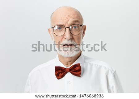 Human facial expressions, emotions, feelings and reaction. Studio shot of attractive unshaven retired man in spectacles having shocked scared look. Bearded European male pensioner expressing fear